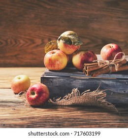 Box with ripe apples and cinnamom on wooden background. Copy-space