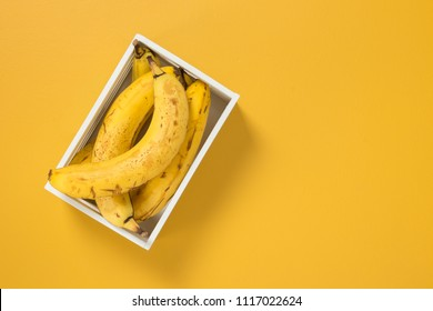Box of ripe bananas on vivid yellow background, with copy space.