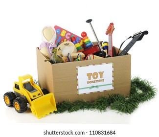 A box with a sign for Christmas toy donations, filled with assorted toys.  On a white background.