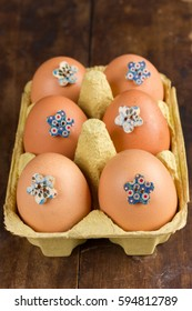 Box with six decorated eggs on wooden background