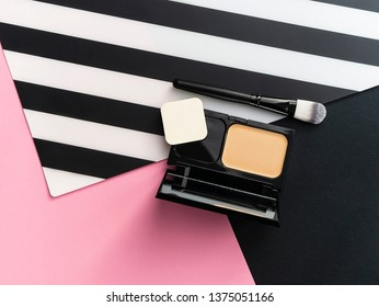 Box with solid foundation and mirror, makeup applicator on pink, white and black stripe background. Mockup for cosmetics.Top view point. Beauty blog concept, minimalistic idea.