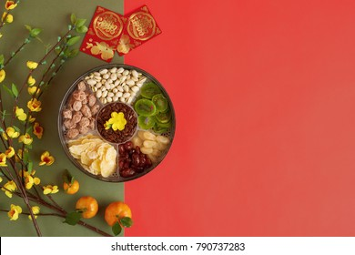 Box with sweet snacks, blooming apricot branches and lucky envelops with best wishes inscription on green and red background