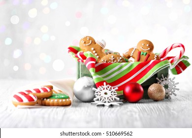 Box with tasty cookies and Christmas decor on light wooden table