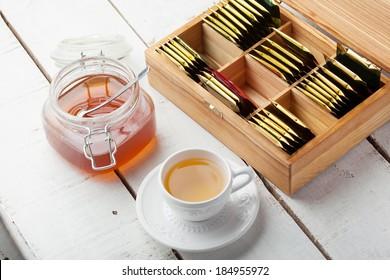 box with tea bag on wooden table, tea cup, honey