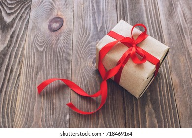 Box tied with a red satin ribbon on wooden background. The festive concept. Selective focus. The horizontal frame. A copy of the places. Toning