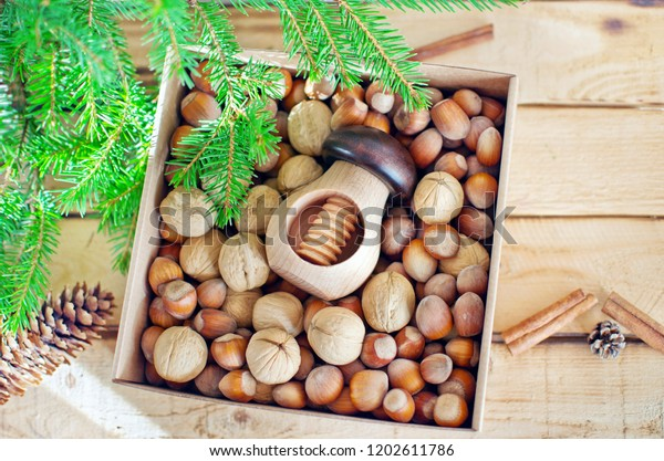 Box with two kind of nuts in shell: walnuts, hazelnuts and mushroom shaped nutcracker on rustic wooden background decorated with fir branch, cones and cinnamon sticks. Healthy Christmas gift concept