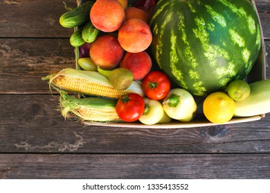 Box with vegetables and fruits on the old wooden background. Top view. Flat lay.