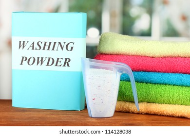 Box of washing powder with blue measuring cup and towels, on wooden table close-up