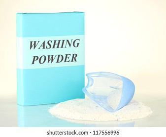 Box of washing powder with blue measuring cup, isolated on white