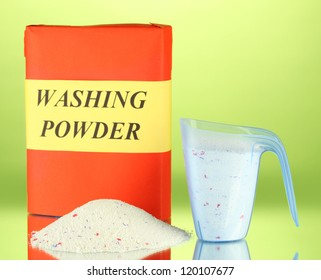 Box of washing powder with blue measuring cup, on green background close-up