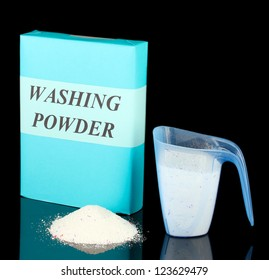 Box of washing powder with blue measuring cup, isolated on black
