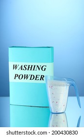 Box of washing powder with blue measuring cup, on blue background close-up
