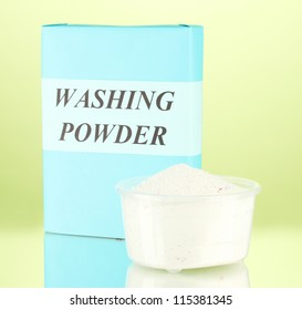 Box of washing powder with measuring cup, on green background close-up