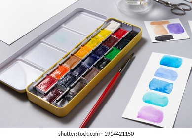 Box of watercolor paints on office desk