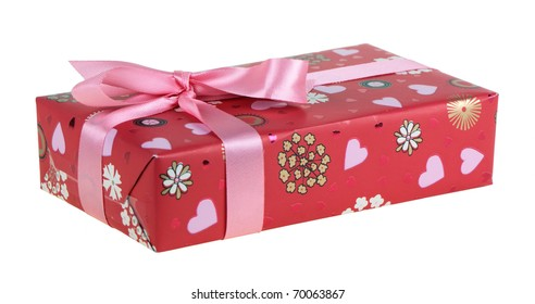 Box wrapped in a red paper and tied up by a pink tape with a bow, isolated on a white background