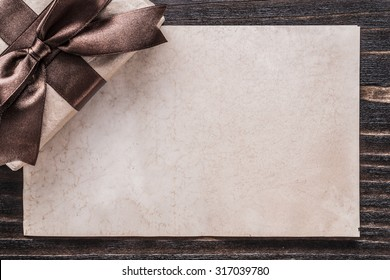 Boxed gift with tied bow paper on vintage wooden board.