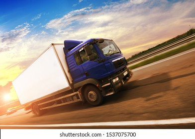 A boxed truck driving fast on the countryside road with green trees and bushes against a night sky with a sunset