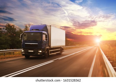 A boxed truck with space for text driving fast on the countryside road against a night sky with a sunset