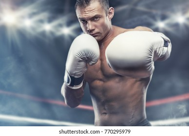 Boxer with an aggressive appearance with boxing white gloves in the ring before the fight