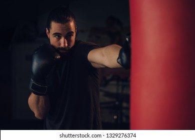 Boxer with beard hitting the heavy bag with front jab