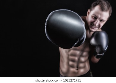 Boxer in boxing gloves directs his hand into the camera on a black background. Boxing concept