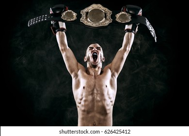 Boxer with Champion belt celebrating flawless victory isolated on black background with copy Space..