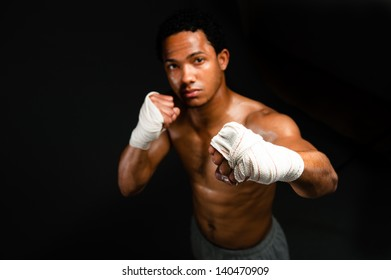 Boxer with dramatic lighting. Powerful fighter portrait-isolated on black background