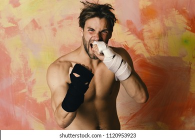 Boxer or karate fighter practices martial arts. Healthy lifestyle and jujitsu concept. Man with wild face and naked torso on colorful background. Guy with black kimono belt and bandage on arms.