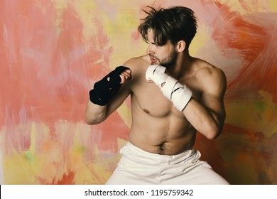 Boxer or karate fighter practices martial arts. Guy with black belt and bandage on arms. Healthy lifestyle and jujitsu concept. Man with busy face and naked torso on colorful background