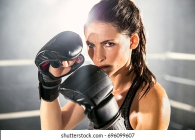 Boxer MMA female fighter posing in confident defensive stance with gloves up
