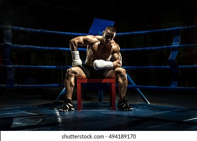 boxer on boxing ring, tired time-out,  black bacground, horizontal photo