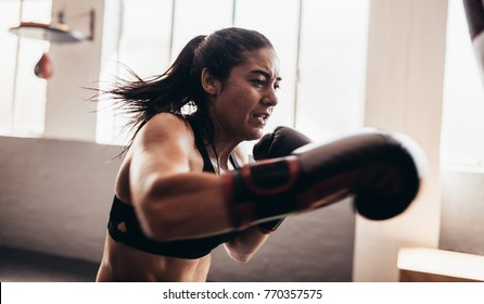 Boxer practicing her punches inside a boxing studio. Close up of a female boxer punching with her boxing gloves on.