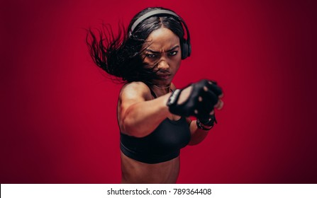 Boxer practicing her punches in a studio. African female boxer practicing boxing against red background.