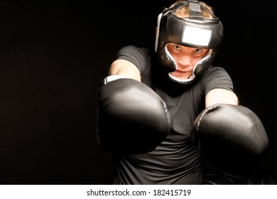 Boxer punching towards the camera with both of his gloved fists with a look of determination, on a dark background with copyspace