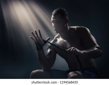 Boxer putting on straps preparing for combat on a dark background