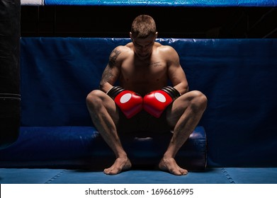 Boxer sits in gloves near the ring with his head bowed. The concept of sports, boxing, mixed martial arts, sports betting. Mixed media