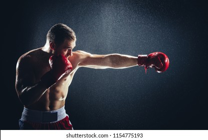Boxer striking a blow in the rain. Professional sport. Fighting. Strength.