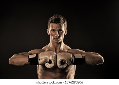 Boxer with strong hands ready to fight. Man athlete with boxing gloves on dark background. Sport, boxing, fitness. Power, action, energy, activity. Health, wellness, bodycare vintage knockout