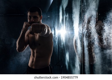 Boxer training in the gym with reflection in low key photo for fight club advertisement