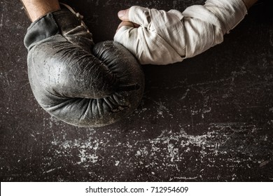 Boxer's hands in the old boxing glove and boxing wrap. Preparation for fight. Dark background. Fight concept. Vintage retro style. Man's strength.