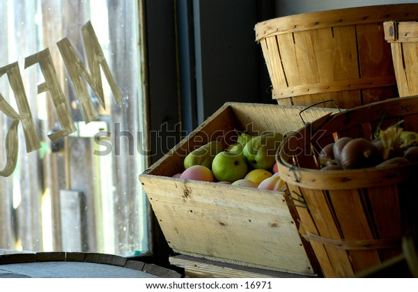 Boxes and barrels of fruit in a merchant store window.