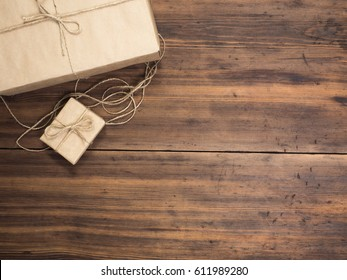Boxes in craft paper, eco paper on the wooden table. Top view. Parcels or gifts tied with twine. Brown paper wrapped gift box with rope bow on a old rustic wood background. Background for your design