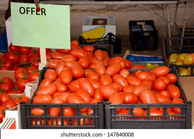 Boxes of freshly harvested organic red tomatoes for sale on a market.