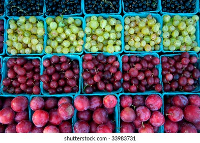 Boxes of just picked gooseberries, plums and currants at local food market
