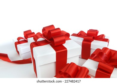 Boxes with presents wrapped in white paper with red ribbons, isolated on white