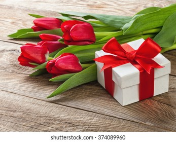 boxes with red ribbons and a bouquet of tulips.
