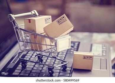 Cajas en un carrito de un teclado portátil. Ideas sobre compras en línea, compras en línea es una forma de comercio electrónico que permite a los consumidores comprar directamente mercadería de un vendedor a través de Internet.
