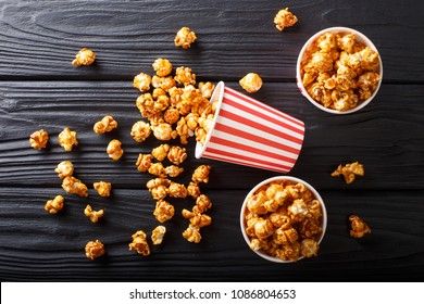 Boxes with wweet caramel popcorn, black background, Snack for cinema closeup. Horizontal top view from above