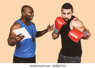 Boxing coach with his fighter against orange background