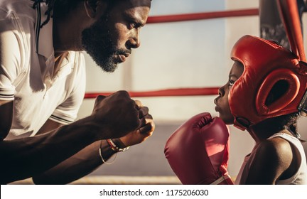 Boxing coach and kid training inside a boxing ring. Close up of a kid in gloves and headgear learning boxing from his coach.